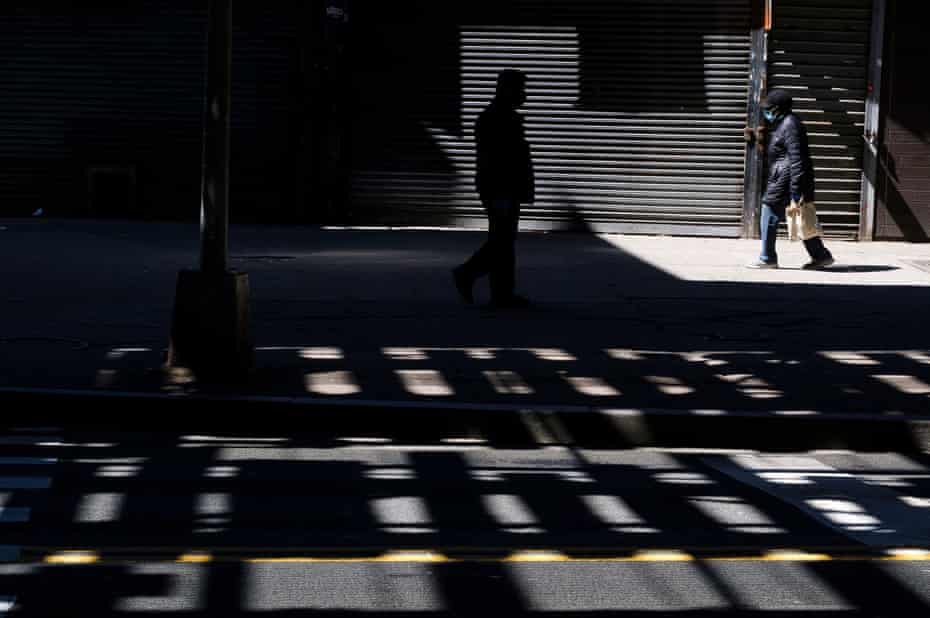 People walk past shuttered store fronts, as all non-essential businesses in the city are closed to help stop the COVID-19 pandemic, in the Bronx, New York.