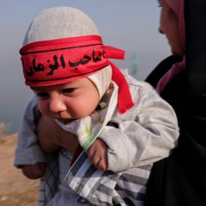 A woman holds her baby, wearing a banner indicating the expectation of the one who must return, a Shia reference to the missing 12th Imam, who must return to earth for the last judgment