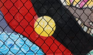 A wire fence in front of an Indigenous flag mural in Darwin, Northern Territory, Australia. January 2017.