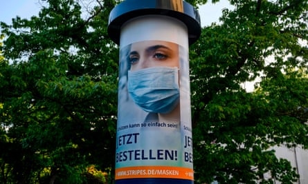 An ad for surgical masks is seen on a column in Berlin