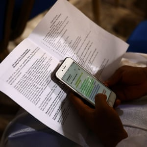 A worshipper reads a passage from the Bible on her smartphone during a Sunday service at the New Jerusalem Parish