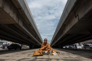 Bangkok, Thailand  A Buddhist monk sits on the ground in between two overpasses as he waits to receive alms