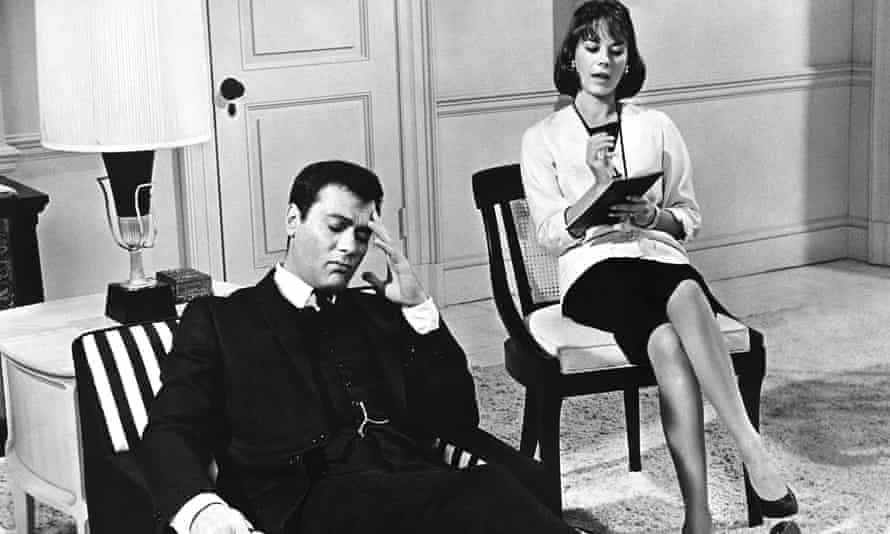 A scene from in Sex and the Single Girl (1964) with Tony Curtis reclining on a couch, one hand touching his temple, his eyes closed, and Natalie Wood sitting on a chair slightly behind him, legs crossed, writing in a notebook.