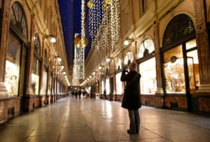 A tourist takes a picture of the empty Gallerie de la Reine, usually one of the most crowded places in the city
