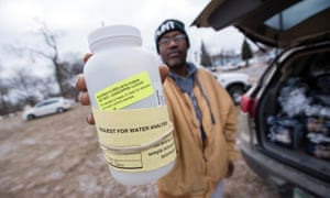 A Michigan resident shows a water testing kit outside a water distribution location in Flint.
