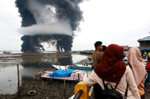 Plumes of black smoke rise from a burning oil spill