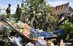 Members of Japan's self-defence force search for survivors in a property in Atsuma