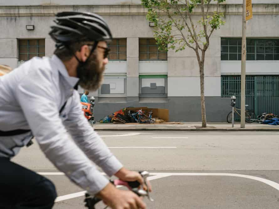 A man rides by a homeless encampment on Howard Street.