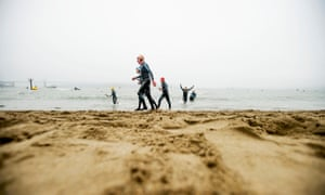 Swimmers emerge from San Francisco Bay following a swim.