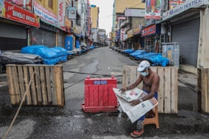 A man reads a newspaper next to closed shops after the government announced an island-wide lockdown