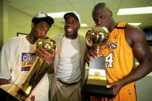 Shaquille O'Neal (R) and Kobe Bryant of the Los Angeles Lakers pose with Lakers legend Magic Johnson after winning the NBA Championship trophy in 2000.