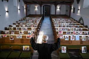 Hamm, Germany: evangelical pastor Klaus-Martin Pothmann stands in front of photos of believers who were asked to send in pictures to represent them among the pews at the St Pankratius church