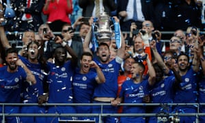 Gary Cahill lifts the trophy as the Chelsea players celebrate.