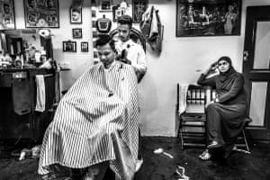 Fitri, one of the senior barbers, working on a client while his wife waits patiently. Son & Dad Barbers, George Town, Penang, Malaysia