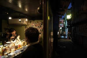 Bar owner Marie Yoshida chats with a patron