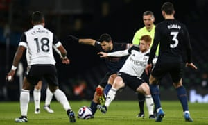 Harrison Reed of Fulham tussles with Sergio Aguero of Manchester City.