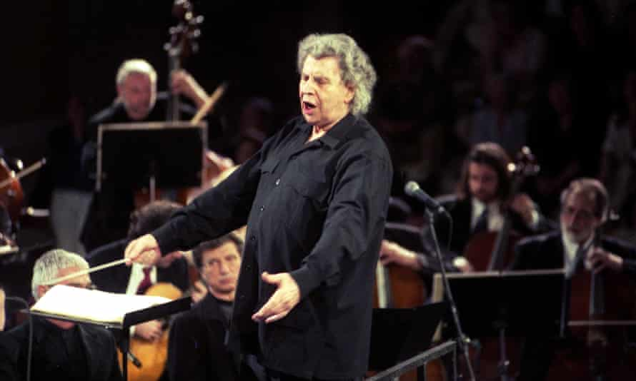 Theodorakis dressed all in black, his eyes closed and both arms low and outstretched with a conductor's baton in one hand, surrounded by orchestral musicians