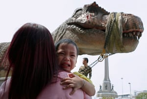 Bangkok, Thailand: A child appears to be frightened by a lifesize model of a T rex