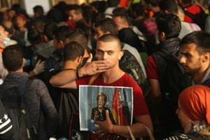 A migrant from Syria holds a picture of Angela Merkel