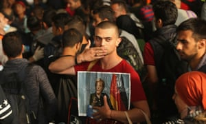 A Syrian refugee with a picture of Merkel after reaching Munich in September 2015.