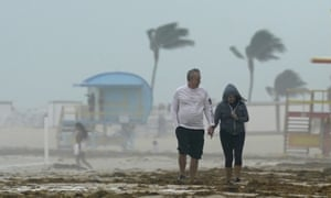 A couple walks along the beach during a downpour on Sunday in Miami.