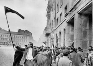 26 October: a rebel flag-bearer triumphantly signals that the state security agency headquarters have been taken and the secret police are ready to come out
