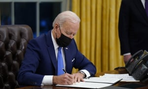 President Joe Biden signs an executive order on immigration in the Oval Office.