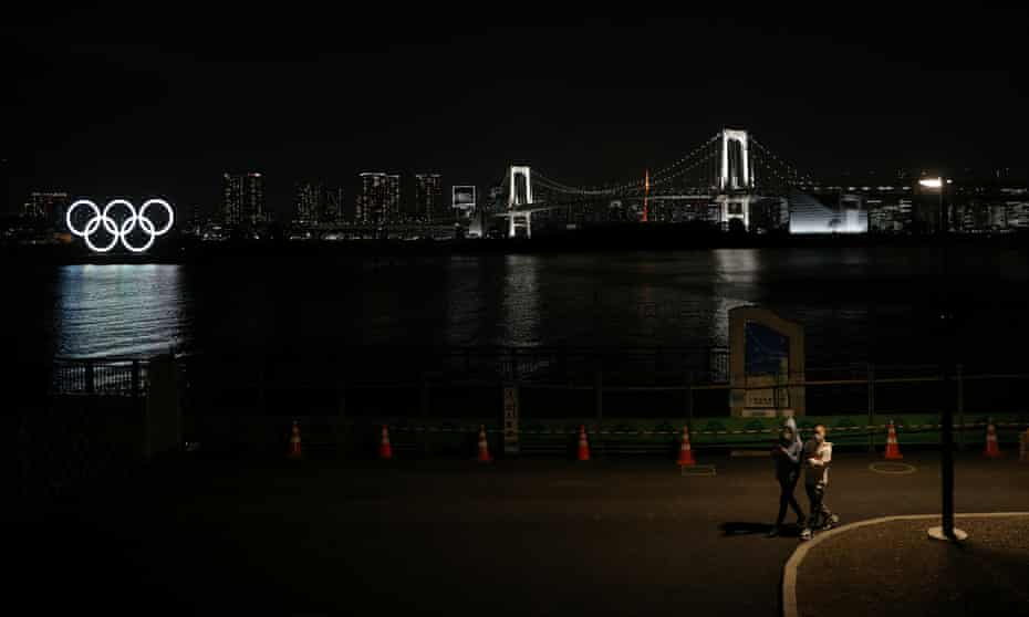 Two men in face masks walk alongside water in Tokyo, with Olympic rings behind them.
