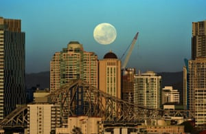 A supermoon sets over the skyline early morning in Brisbane