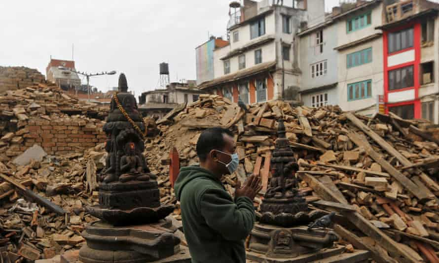 A man prays next to rubble of a temple, destroyed in Saturday's earthquake, in Kathmandu.