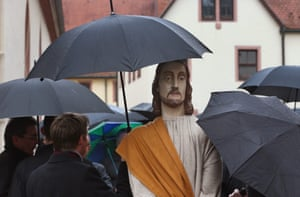People shelter a figure of Jesus with an umbrella in Lohr am Main, Germany