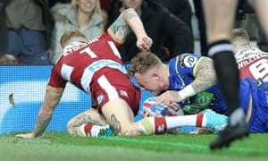 Josh Charnley of Warrington Wolves beats Sam Tomkins of Wigan Warriors to go over for the first try of the match.
