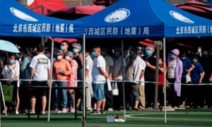 People who live near or have visited the Xinfadi food market wear masks while queueing for testing at the Guang'an sports centre in Beijing