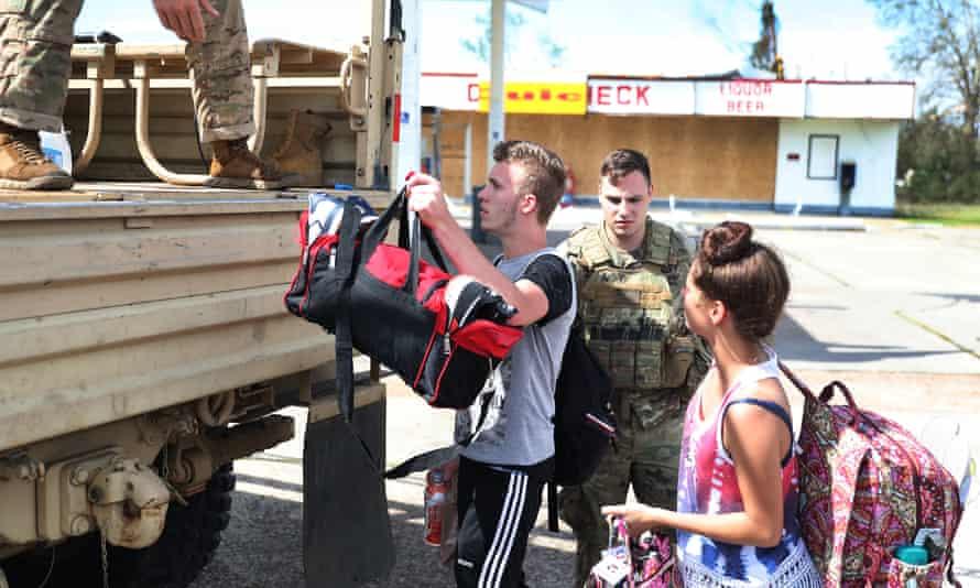 Caleb Daigle and Cloe Cuvilliara are evacuated by Louisiana national guard members after Hurricane Laura passed through Lake Charles.