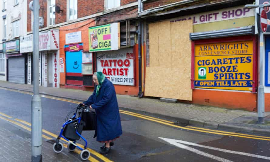 A woman pushes her shopping trolley past boarded-up shops in Blackpool