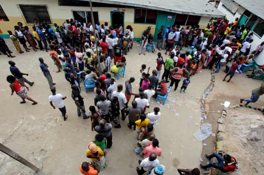 People wait to vote at a polling station in Monrovia.