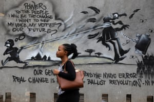 Nairobi, KenyaA woman walks past a wall of graffiti in the central business district