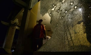 A labourer inspects the damage done to glass windows next to the site of a bomb attack in the upscale resort town of Hua Hin in Thailand.