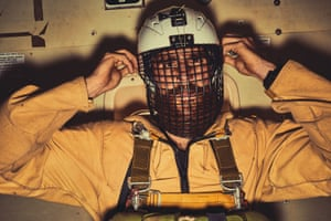 A firefighter aboard a plane adjusts his helmet before a leap