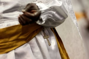 A cross sits on the waist of a worshipper as she prays during an Easter Sunday service.