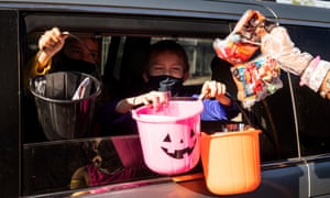 Children wearing a face mask trick-or-treat from the back of their car during a Halloween drive-thru trick-or-treat event organized by the various city services during the coronavirus pandemic at Highland Park in Monterey Park, California, USA, 29 October 2020.