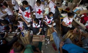 Mexican Red Cross workers treat the blistered and cut feet of Central American migrant. Mexico has offered ID papers and jobs to those registering for asylum.