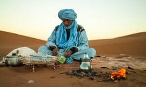 A Bedouin sitting in the dessert making tea