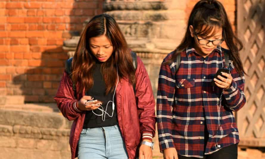 Nepalese women use their mobile phones in Bhaktapur, south-east of Kathmandu