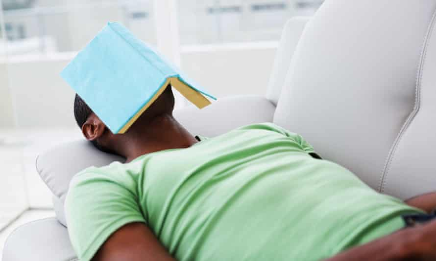 Relaxed man with book over face lying on sofa