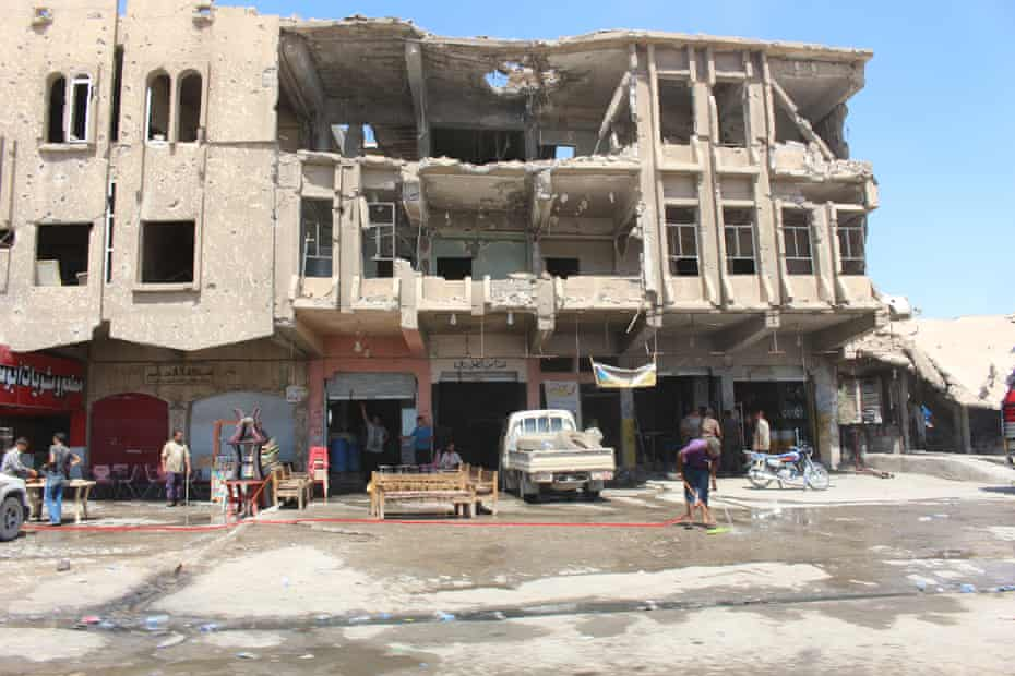 Shop owners outside a damaged building in new Mosul.