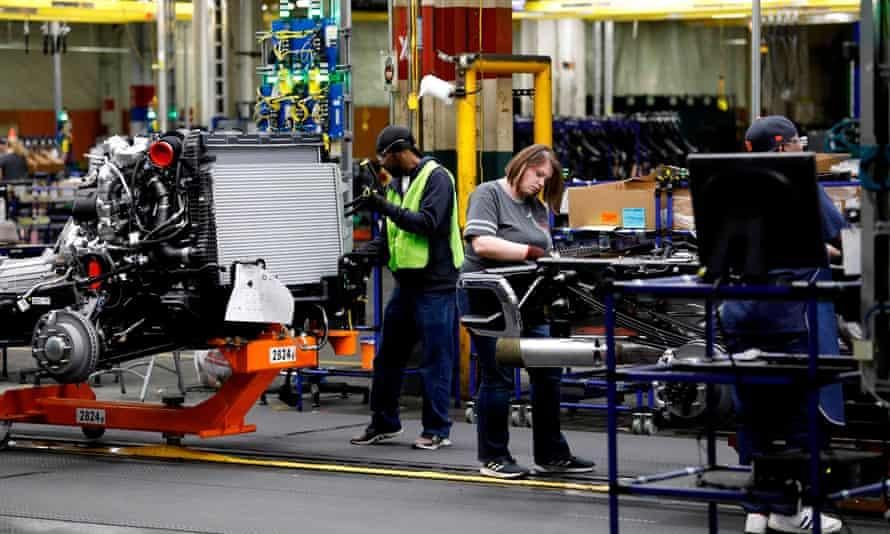 Workers work on General Motors pickup trucks in Flint, Michigan, in 2019.