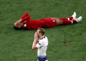 Liverpool's Virgil van Dijk celebrates winning the Champions League Final as Tottenham's Harry Kane looks dejected.