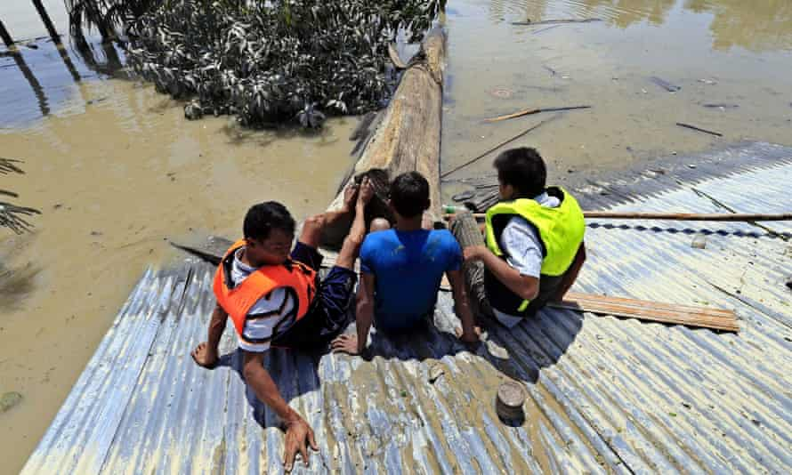 Men try to shift a log from a roof in Kale township, Sagaing, Burma