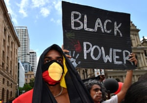 Thousands turn out for an Invasion Day rally in Brisbane with signs including 'Black power' and 'colonialism cooked this country'.